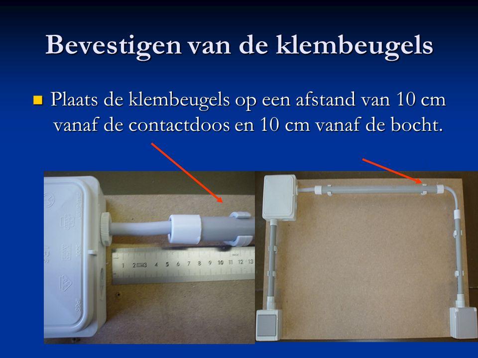 Bevestigen van de klembeugels Plaats de klembeugels op een afstand van 10 cm vanaf de contactdoos en 10 cm vanaf de bocht. Plaats de klembeugels op ee