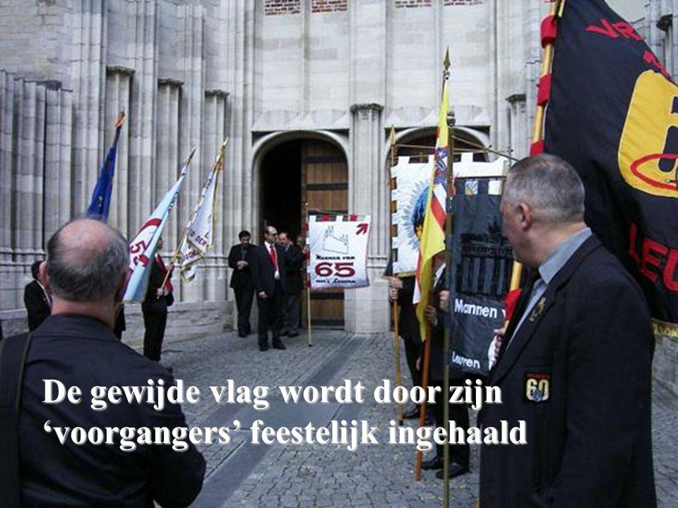 De gewijde vlag wordt door zijn 'voorgangers' feestelijk ingehaald