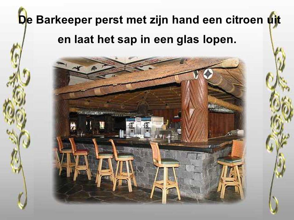 De Barkeeper perst met zijn hand een citroen uit en laat het sap in een glas lopen.
