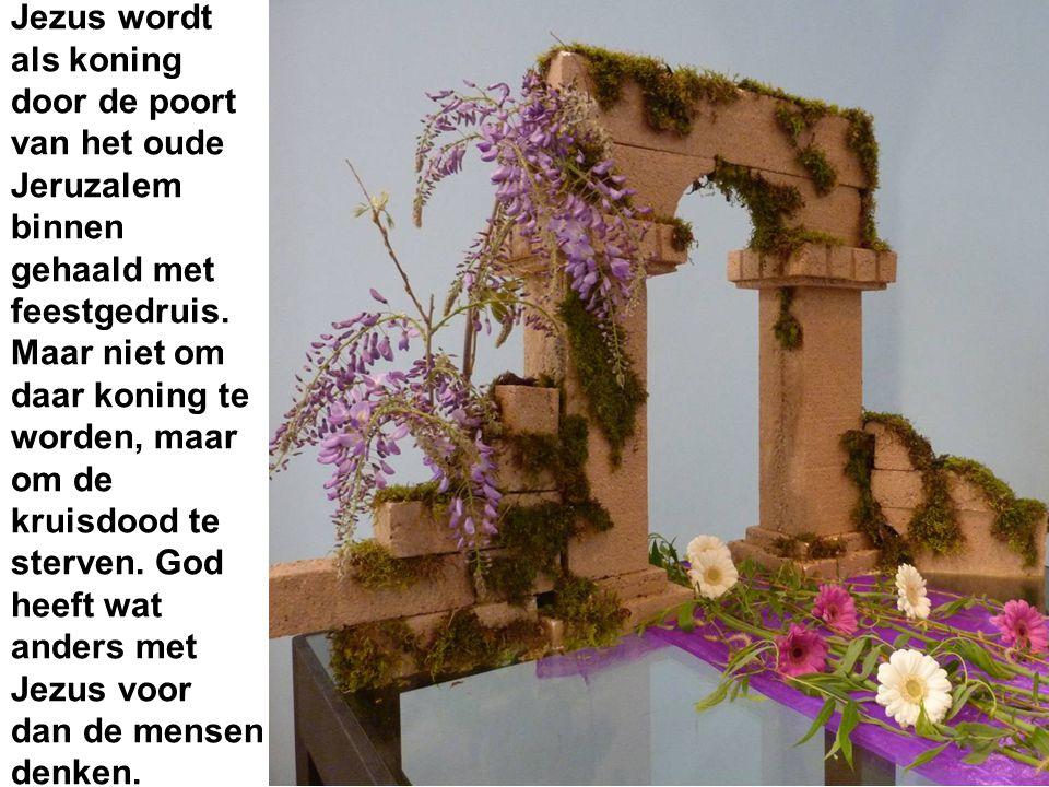 Jezus wordt als koning door de poort van het oude Jeruzalem binnen gehaald met feestgedruis.