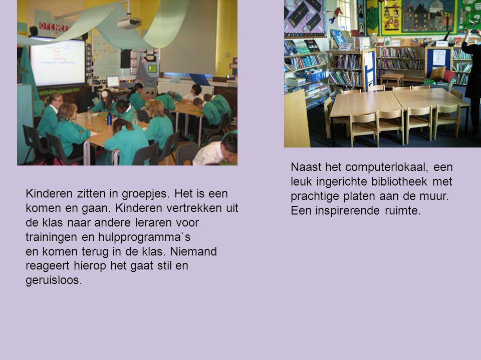 Naast het computerlokaal, een leuk ingerichte bibliotheek met prachtige platen aan de muur. Een inspirerende ruimte. Kinderen zitten in groepjes. Het