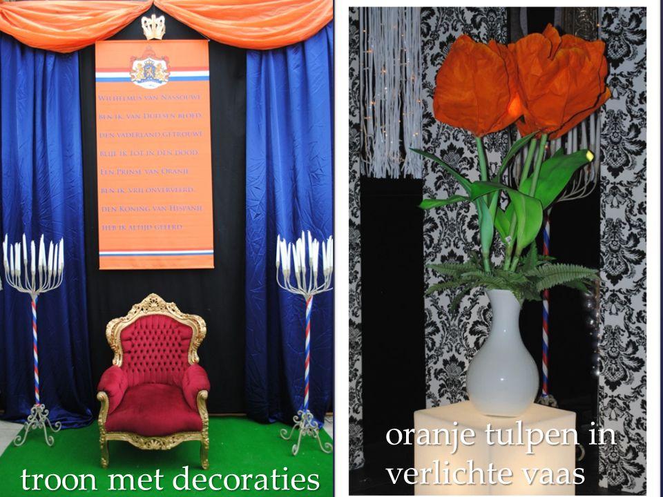 troon met decoraties oranje tulpen in verlichte vaas
