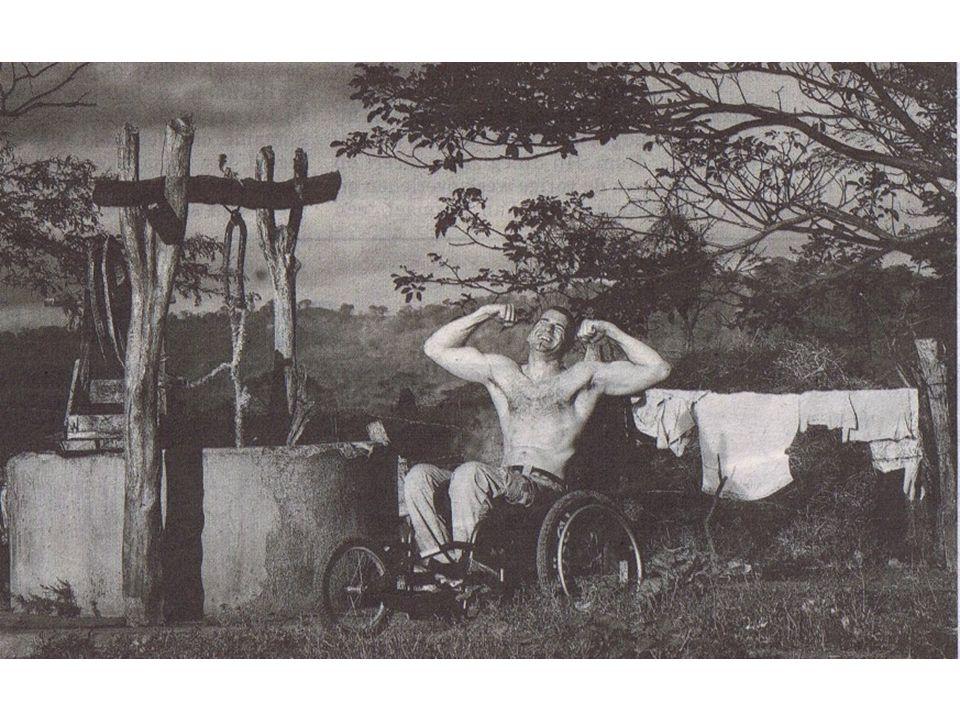 Bij een waterput, met een stel kippen, een varken, een ezel en drogend wasgoed op de achtergrond, zit Henk aan zijn ontbijt van bonen en rijst, De fotografe Lieve Blanquaert wil graag zijn prachtige, door het handbiken gespierde bovenlichaam mooi in beeld.