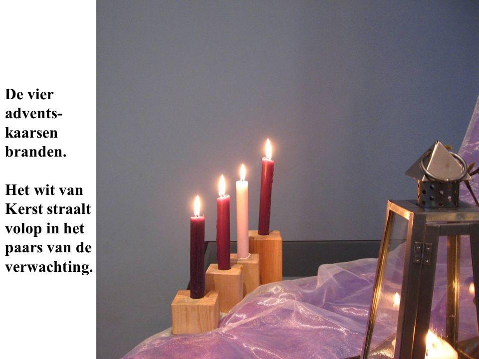 De vier advents- kaarsen branden. Het wit van Kerst straalt volop in het paars van de verwachting.