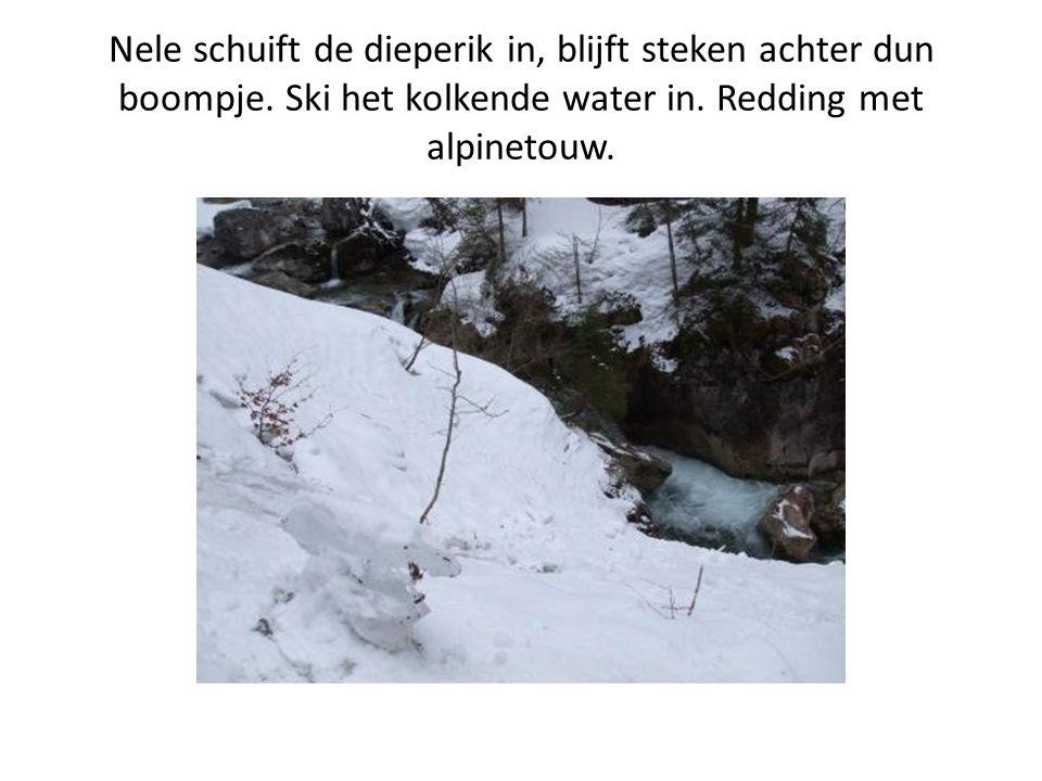 Nele schuift de dieperik in, blijft steken achter dun boompje. Ski het kolkende water in. Redding met alpinetouw.