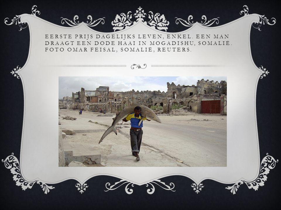EERSTE PRIJS DAGELIJKS LEVEN, ENKEL.EEN MAN DRAAGT EEN DODE HAAI IN MOGADISHU, SOMALIË.