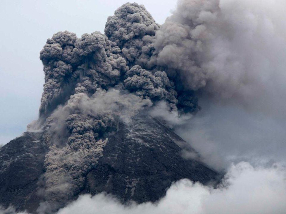 Lichamen van de slachtoffers van een uitbarsting van de Merapi onder as en puin in de voorkant van een huis in Argomulyo, 5 november 2010