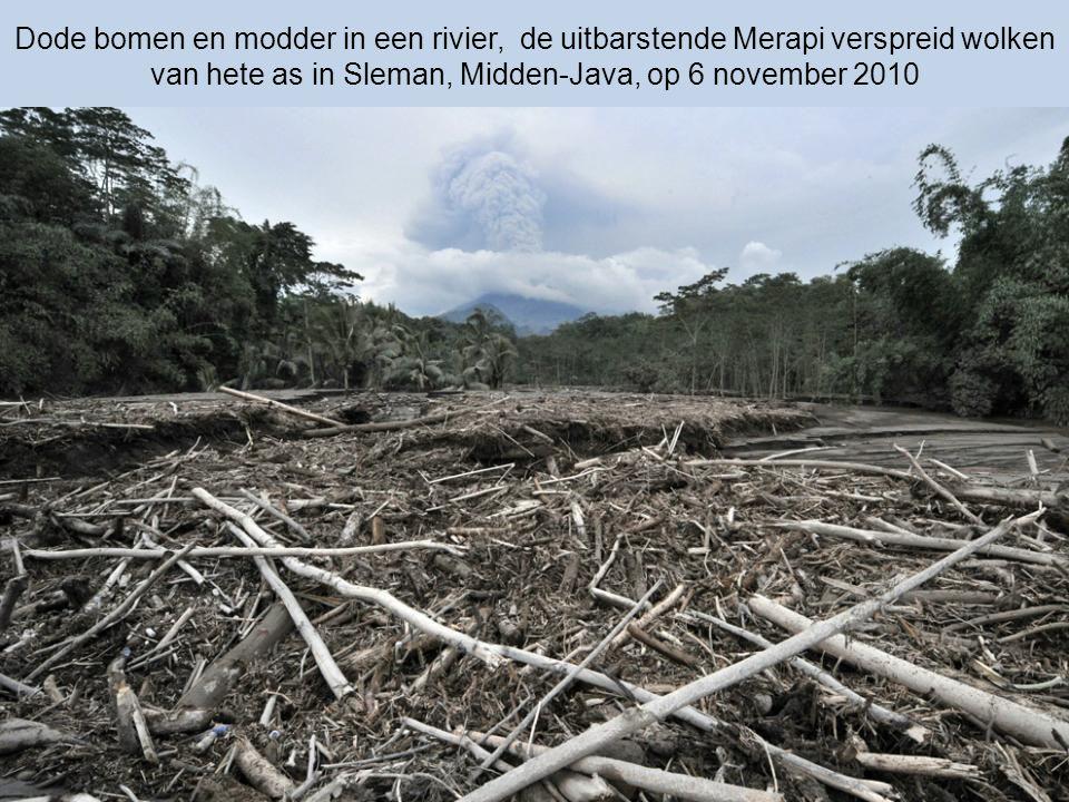 Dode bomen en as, een beschadigd huis door de uitbarstende Merapi, (op de achtergrond) 6 november 2010