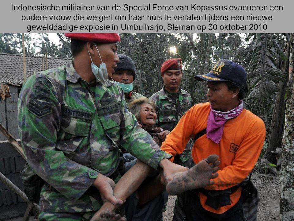 Indonesische militairen van de Special Force van Kopassus evacueren een oudere vrouw die weigert om haar huis te verlaten tijdens een nieuwe gewelddadige explosie in Umbulharjo, Sleman op 30 oktober 2010