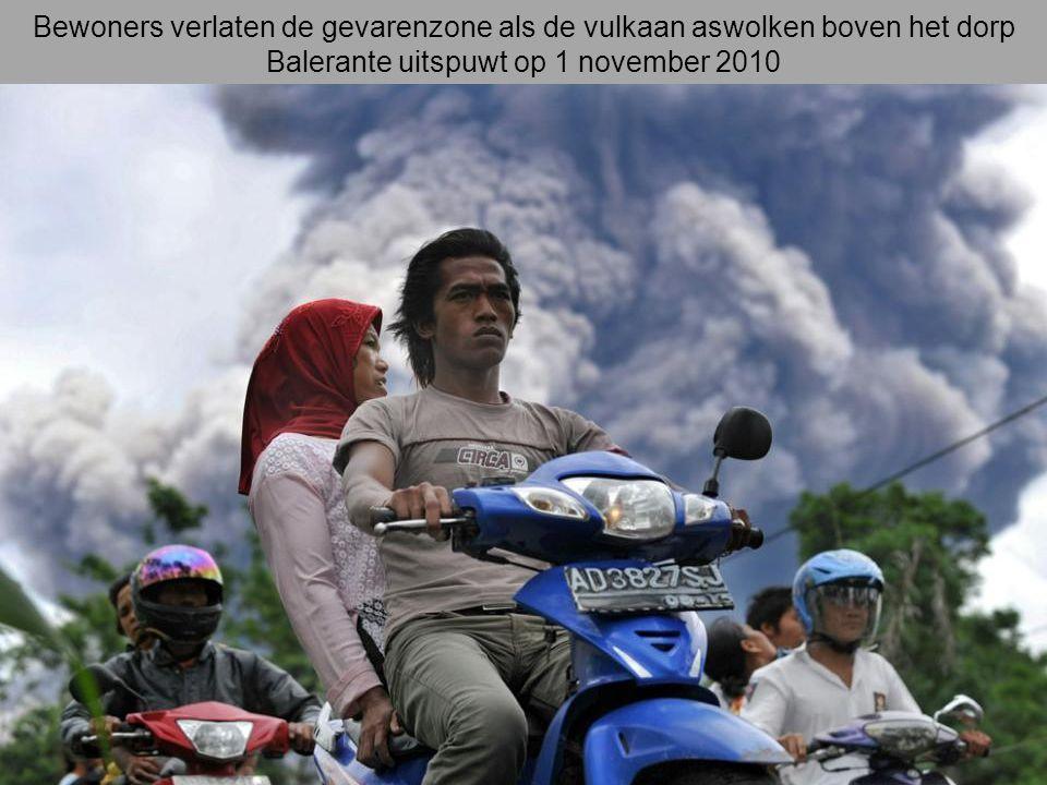 Bewoners verlaten de gevarenzone als de vulkaan aswolken boven het dorp Balerante uitspuwt op 1 november 2010