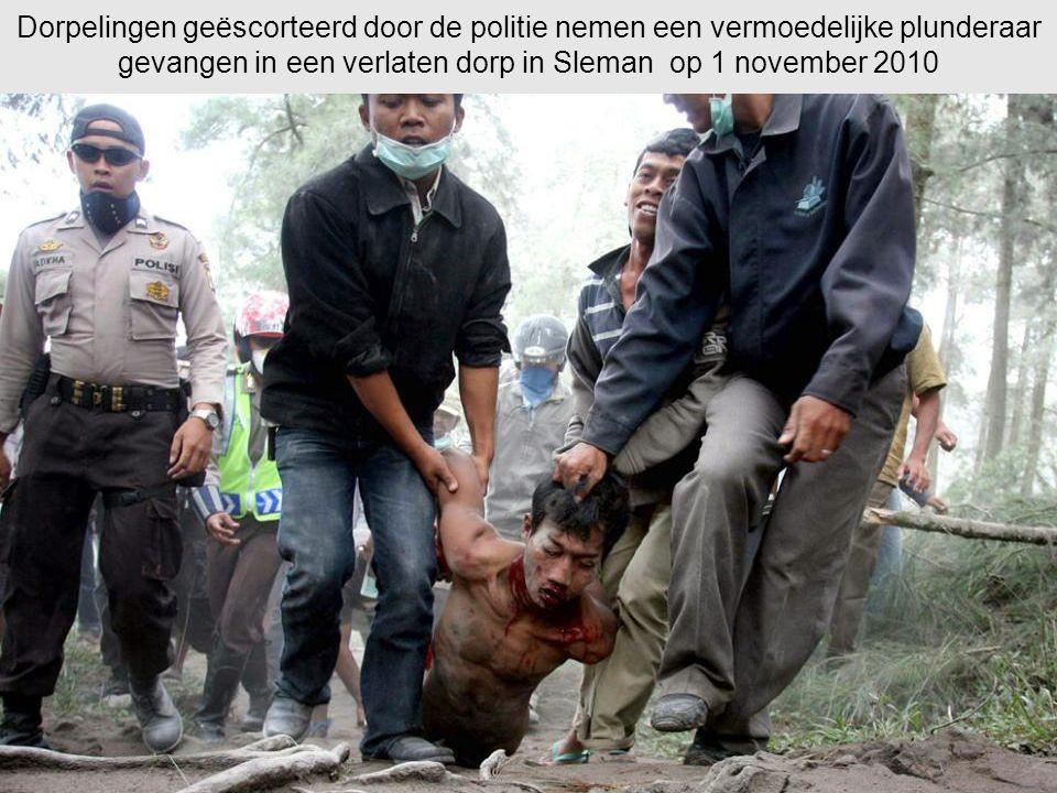Dorpelingen geëscorteerd door de politie nemen een vermoedelijke plunderaar gevangen in een verlaten dorp in Sleman op 1 november 2010
