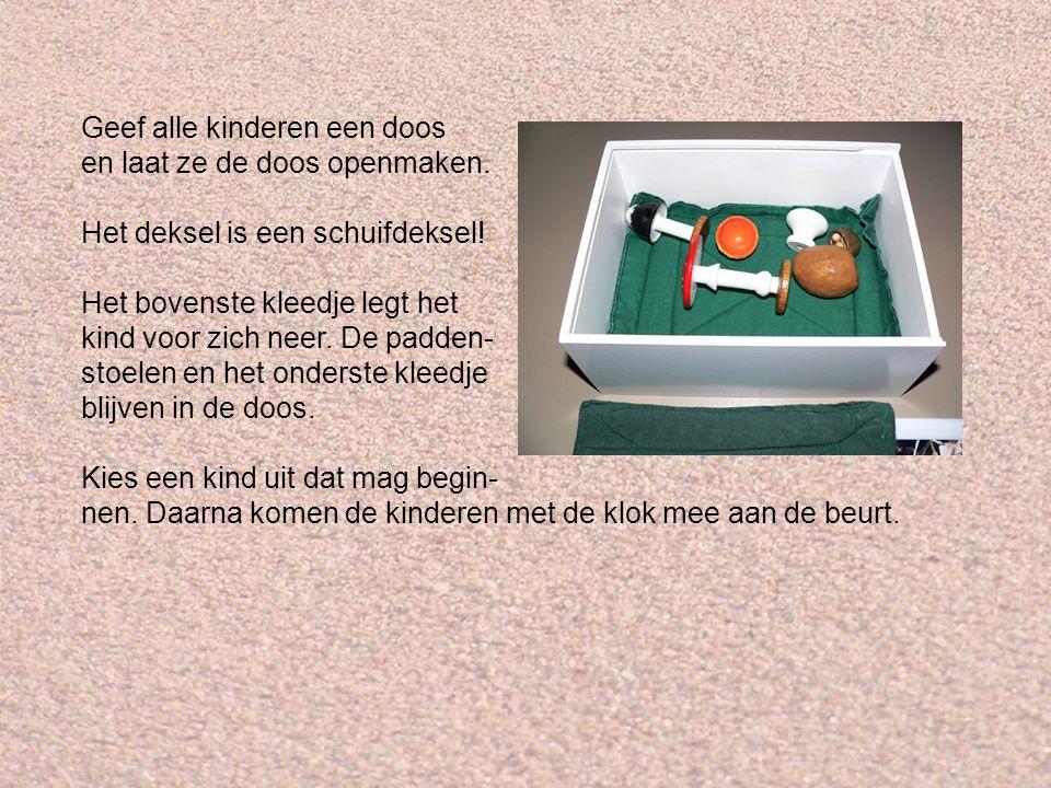 Geef alle kinderen een doos en laat ze de doos openmaken. Het deksel is een schuifdeksel! Het bovenste kleedje legt het kind voor zich neer. De padden