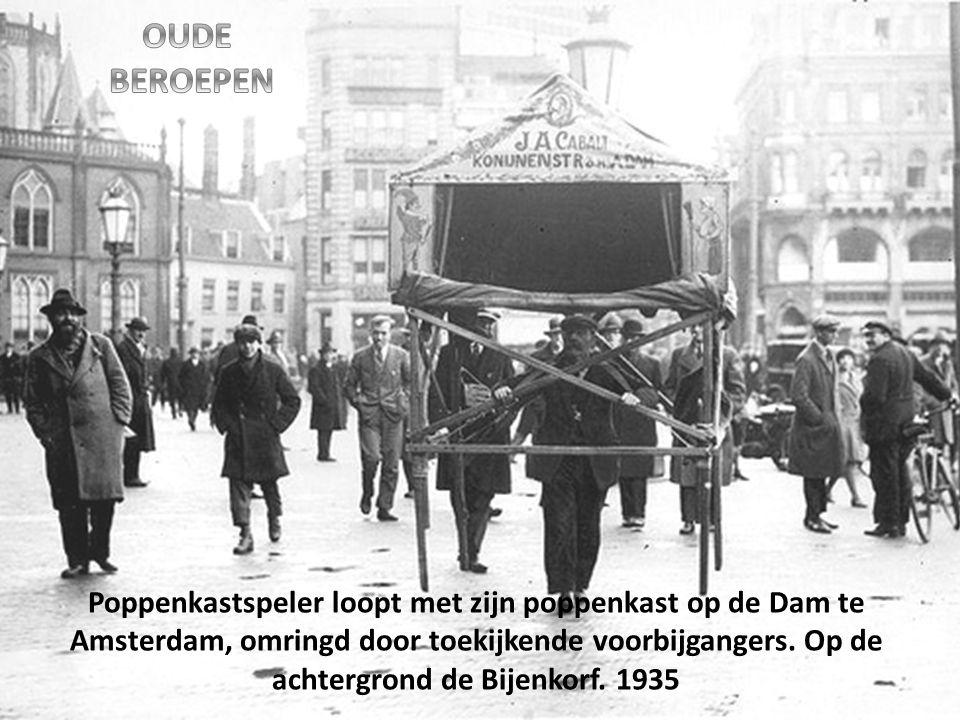 Poppenkastspeler loopt met zijn poppenkast op de Dam te Amsterdam, omringd door toekijkende voorbijgangers.