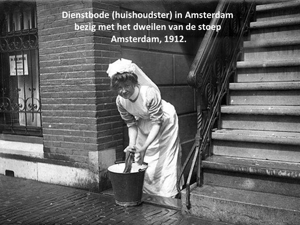 Dienstbode (huishoudster) in Amsterdam bezig met het dweilen van de stoep Amsterdam, 1912.