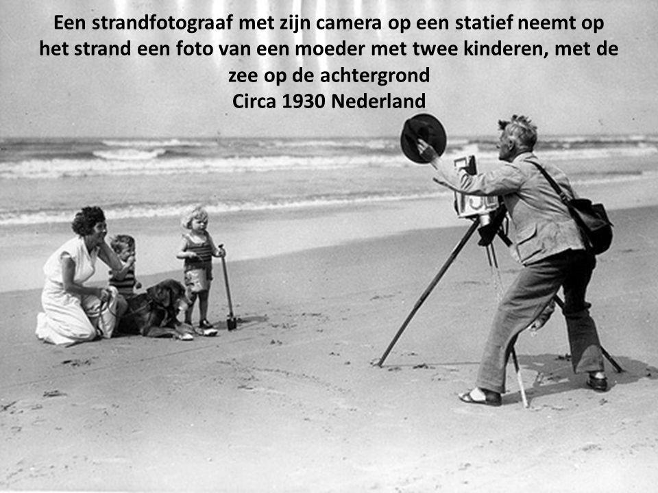 Een strandfotograaf met zijn camera op een statief neemt op het strand een foto van een moeder met twee kinderen, met de zee op de achtergrond Circa 1930 Nederland