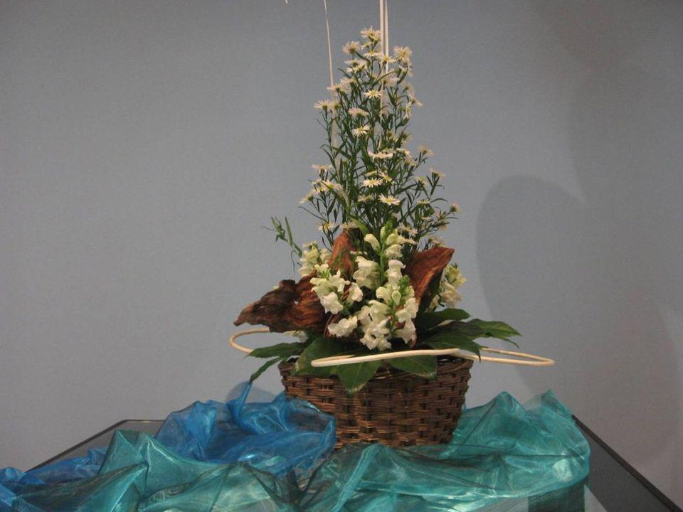 Het bloemstuk is gemaakt in een mand, zoals Mozes in een mand van papyrus lag in het water van de Nijl.
