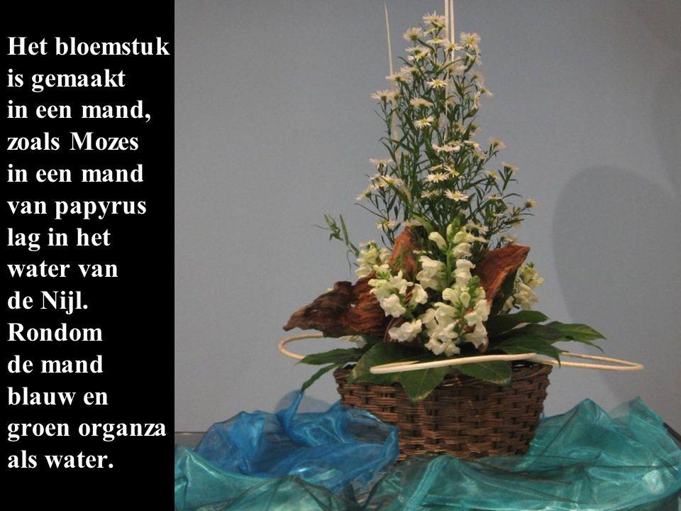 Het bloemstuk is gemaakt in een mand, zoals Mozes in een mand van papyrus lag in het water van de Nijl. Rondom de mand blauw en groen organza als wate