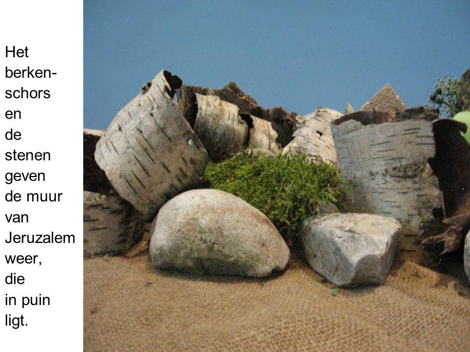 Het berken- schors en de stenen geven de muur van Jeruzalem weer, die in puin ligt.