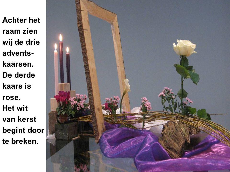 Achter het raam zien wij de drie advents- kaarsen. De derde kaars is rose. Het wit van kerst begint door te breken.