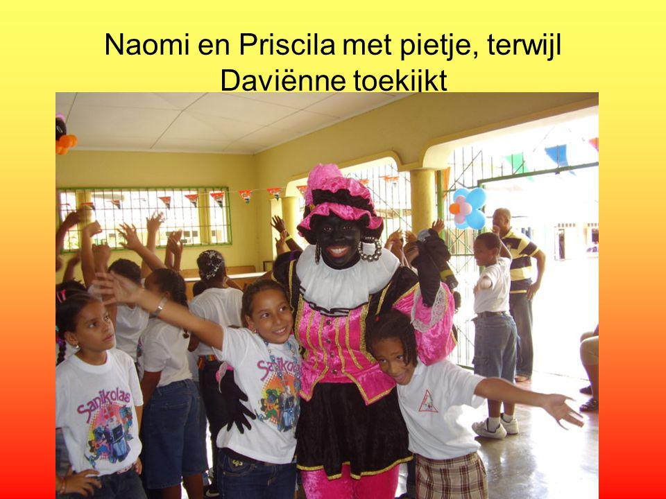 Naomi en Priscila met pietje, terwijl Daviënne toekijkt