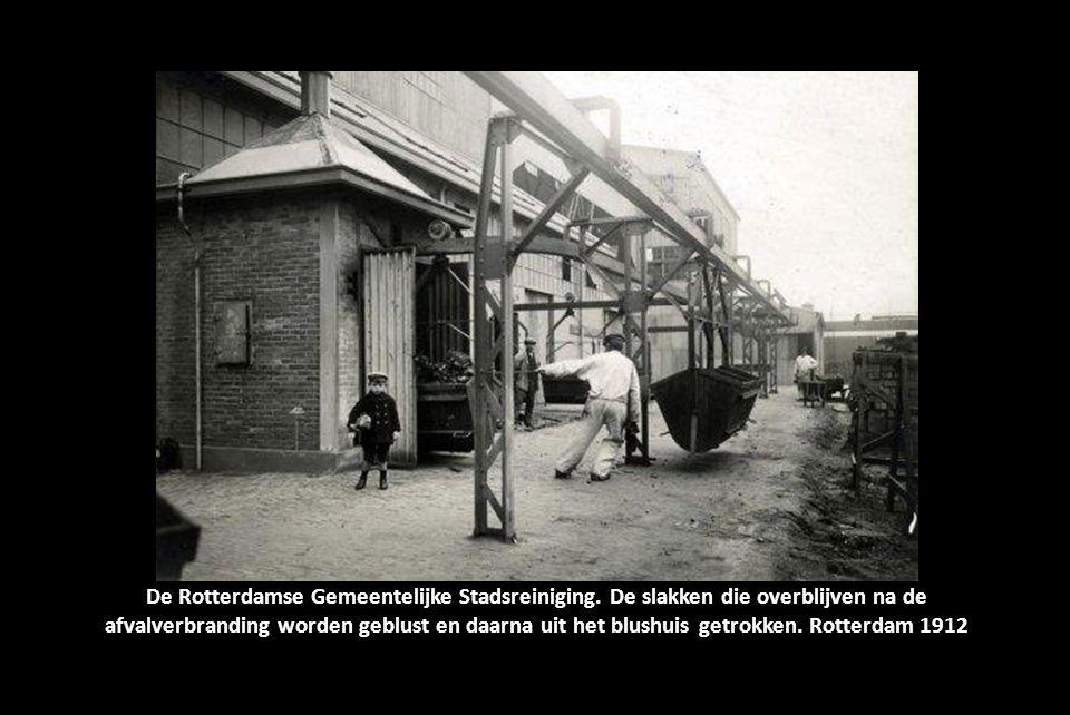 De Rotterdamse Gemeentelijke Stadsreiniging. De machinekamer van het bedrijf met de grote schoorsteen. Verderop in de hal staan twee mannen. Rotterdam