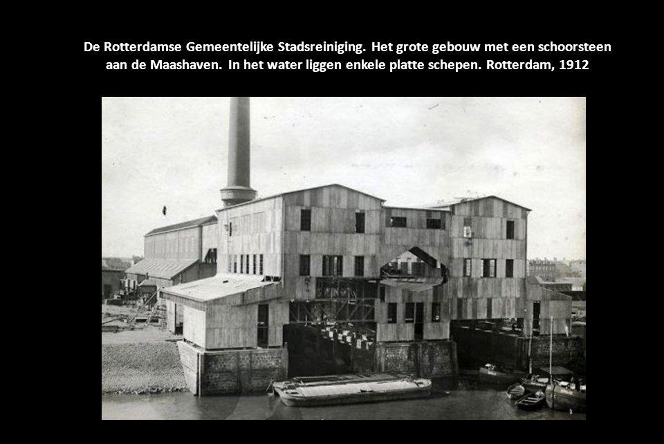 De Rotterdamse Gemeentelijke Stadsreiniging Een rij van 40 verbrandingsovens in een hal. Mannen met witte overalls zijn er aan het werk. Rotterdam, Ne