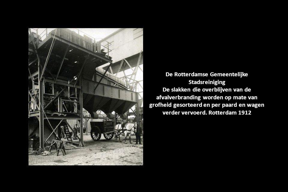 De Rotterdamse Gemeentelijke Stadsreiniging. Het grote gebouw met een schoorsteen aan de Maashaven. In het water liggen enkele platte schepen. Rotterd