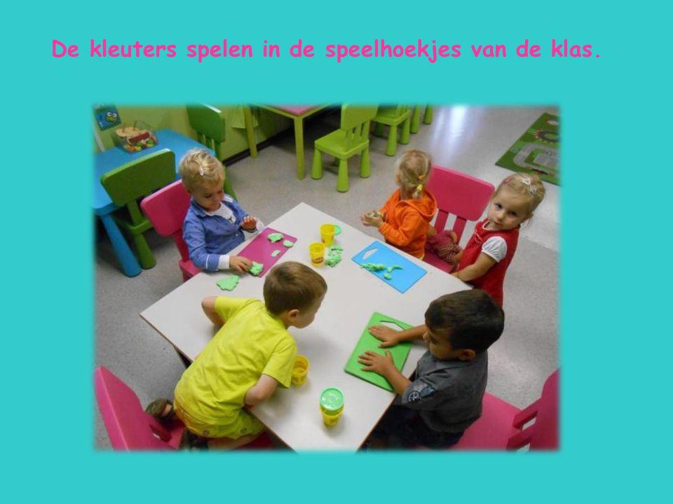 De kleuters spelen in de speelhoekjes van de klas.