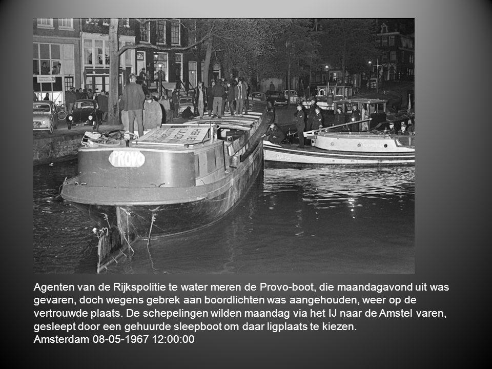 Agenten van de Rijkspolitie te water meren de Provo-boot, die maandagavond uit was gevaren, doch wegens gebrek aan boordlichten was aangehouden, weer