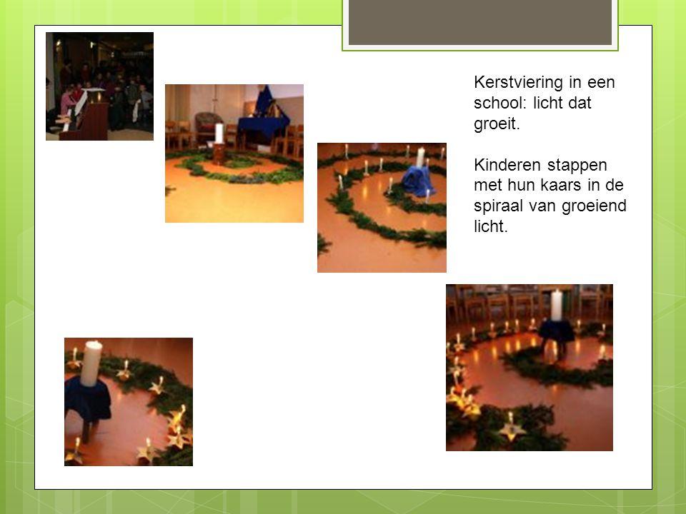 Kerstviering in een school: licht dat groeit. Kinderen stappen met hun kaars in de spiraal van groeiend licht.